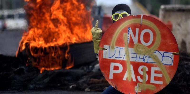 Un manifestante sostiene un aviso durante una protesta en Cali