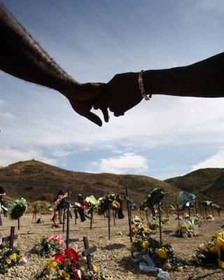 Dos haitianos se estrechan la mano ante un cementerio en recuerdo a las víctimas del terremoto de hace un año.