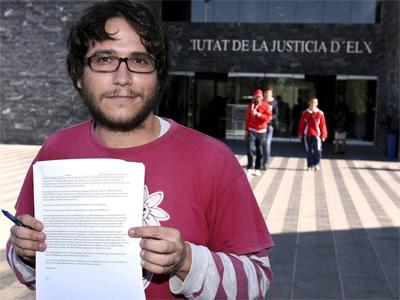 Adrián Vaíllo, del Movimiento Antimilitarista Tortuga, muestra el escrito que ha presentado en el registro de los juzgados de Elche.-EFE/Morell