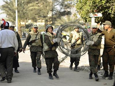 Soldados egipcios retiran, ayer, las alambradas de espinos que bloqueaban los accesos a la plaza Tahrir de El Cairo. REUTERS