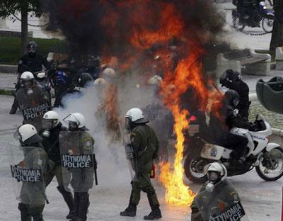 Policías en Atenas entre llamas.