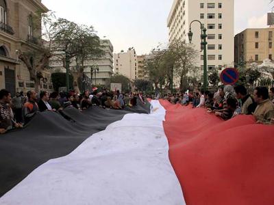 Manifestantes que protestan contra el presidente Hosni Mubarak sostienen una bandera egipcia gigante mientras se concentran en la calle del Parlamento egipcio, en El Cairo./ EFE