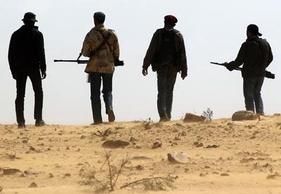 Un grupo de jóvenes rebeldes libios, en la carretera que une Bengasi, su capital, con la estratégica ciudad de Ajdabiya, donde prosiguen los combates. g. tomasevic /reuters