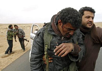 Combatientes rebeldes, heridos ayer por los bombardeos en una carretera junto a Ras Lanuf. - REUTERS