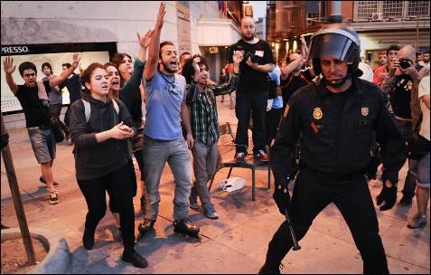 Varios jóvenes increpan a un policía durante la accidentada jornada de la manifestación.