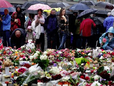 Varias personas dejan flores en la entrada de la catedral de Oslo. REUTERS