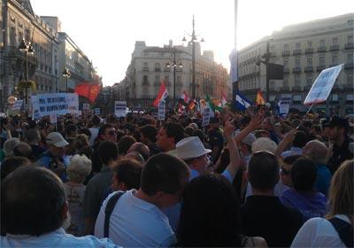 Imagen de la Puerta de Sol con los manifestantes y peregrinos, separados por la Policía, portando sus diferentes proclamas y banderas. -