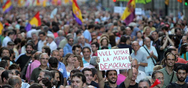Miles de ciudadanos han salido a la calle en Barcelona. En la imagen, un joven sostiene un pancarta con el lema 'Quiero votar mi democracia'. EFE/Toni Albir