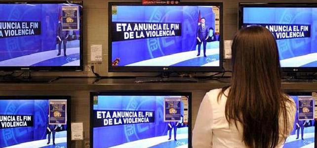 Una mujer contempla ante el escaparate de una tienda la noticia del final de la actividad armada de ETA. EFE.