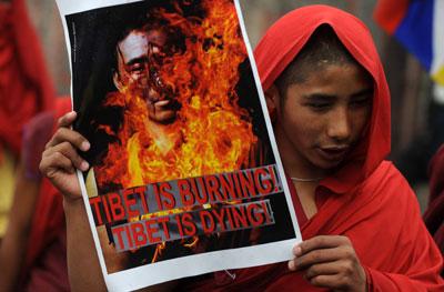 '¡Tíbet arde! ¡Tíbet se muere!', dice el cartel de este joven monje budista en una marcha en Siliguri.-
