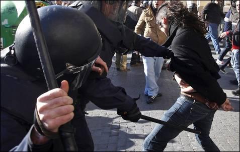 Una joven es golpeada por la policía, que no ha dudado en utilizar las porras para dispersar a los estudiantes en el centro de Valencia.