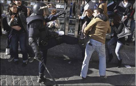 Un antidisturbios da una patada a un manifestante.