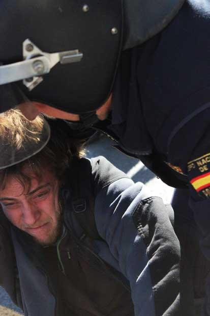 Un policía carga contra uno de los manifestantes reunidos el lunes en Valencia.