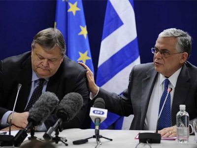 El ministro de Finanzas griego, Venizelos, y el presidente del país, Papadimos, ayer tras el acuerdo. AFP