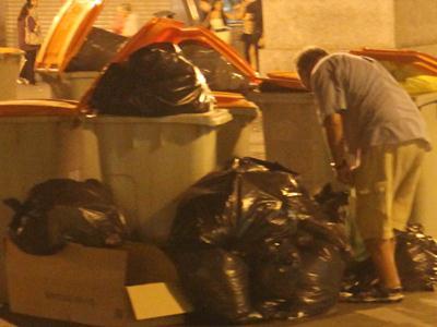 Un hombre busca en la basura en un barrio céntrico de Madrid - E.M.