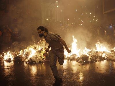 Un miembro del grupo 'Black Block' se aleja de la sede de la Asamblea Municipal durante las últimas protestas en Río, 7 de octubre de 2013 REUTERS/Ricardo Moraes
