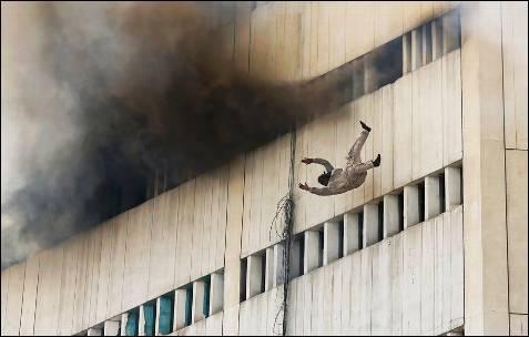 Un hombre cae de un piso alto de un edificio en llamas en el centro de Lahore (Pakistán).