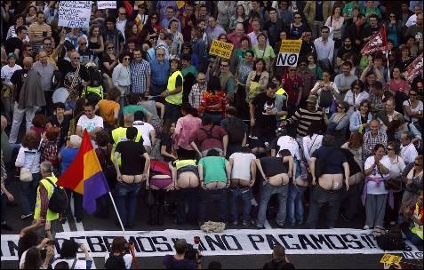Varios manifestantes se bajan los pantalones durante la manifestación contra la troika en Madrid.