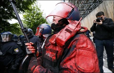 Un policía machado con pintura roja arrojada por los manifestantes en el cerco del movimientos Blockupu al BCE en Frankfurt, Alemania.