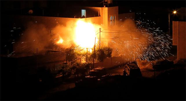 La casa de Amar Abu Eysha, uno de los sospechosos de secuestrar a los tres jóvenes israelíes, arde en llamas tras un ataque del ejército israelí en Halhoul cerca de Hebrón.