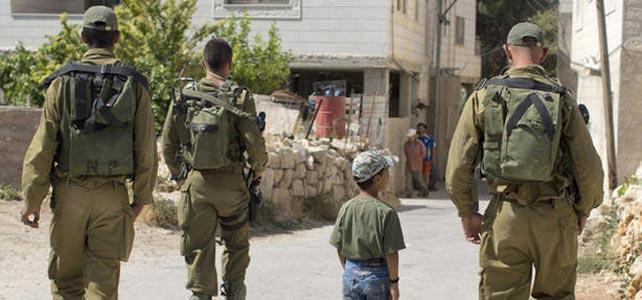 Un niño Palestino camina rodeado por soldados del Ejército israelí.