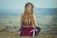 Chica fotografiada de espaldas, relajándose en plena naturaleza