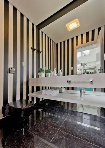 Banheiro com parede listradas e piso para banheiro escuro