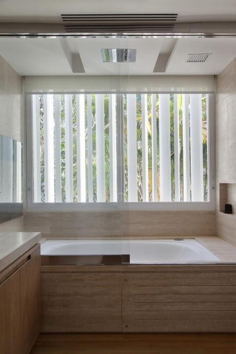 Banheiro de luxo com banheira revestida com madeira Projeto de Gisele Taranto