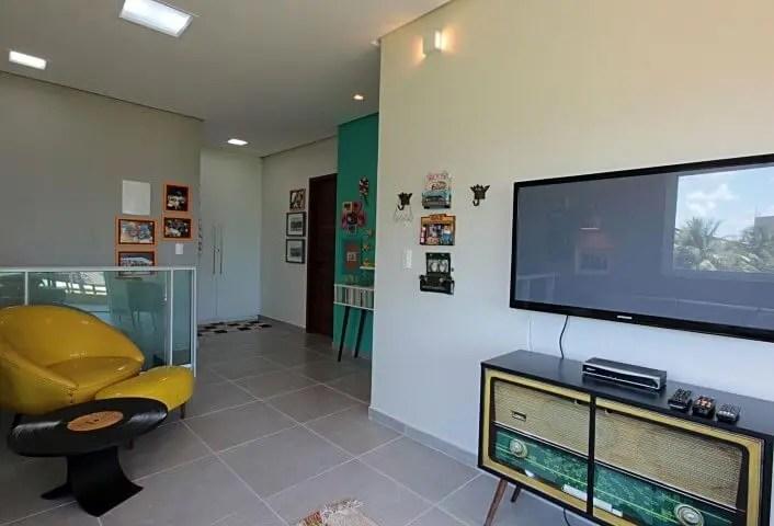 Sala de TV com rack retrô com foto de rádio Projeto de Celia Beatriz