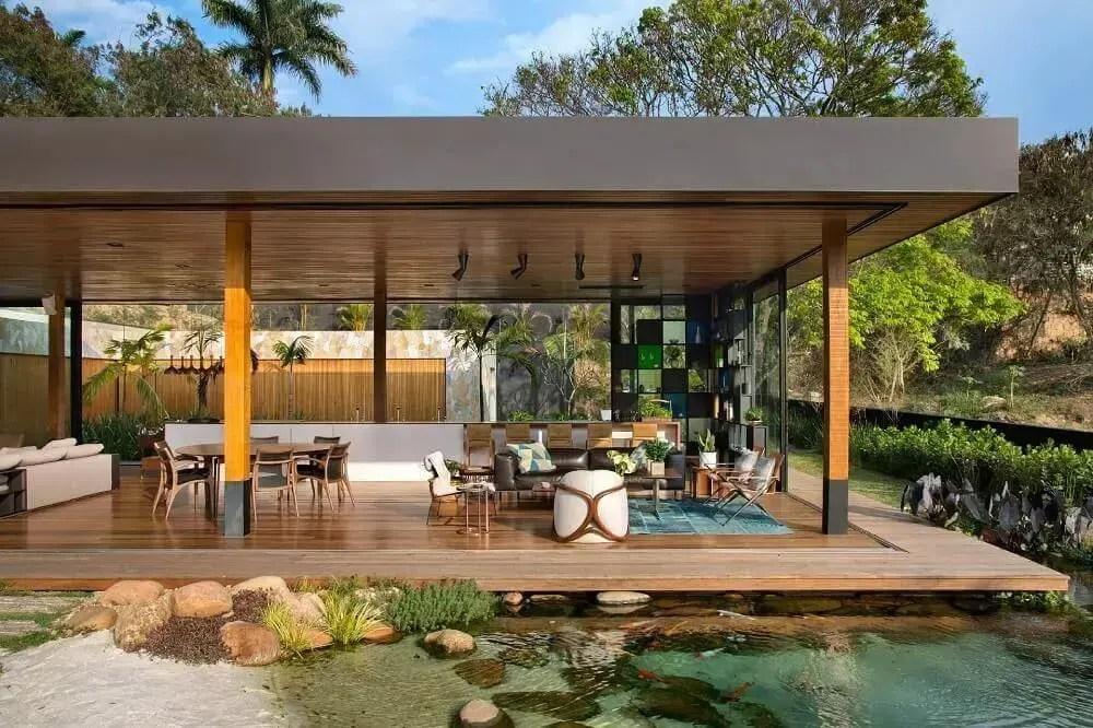 sofisticada varanda de área gourmet externa com lago