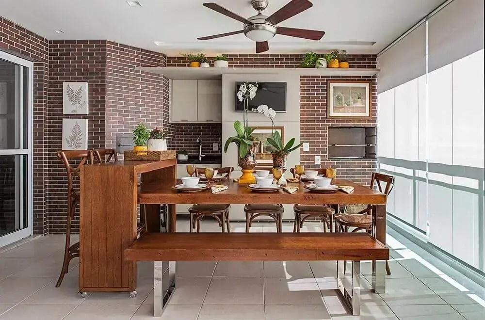 tijolo à vista e mesa de madeira em area gourmet de apartamento