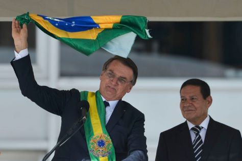 Presidente Jair Bolsonaro e o vice-presidente Hamilton Mourão exibem uma bandeira nacional durante discurso no parlatório do Palácio do Planalto.