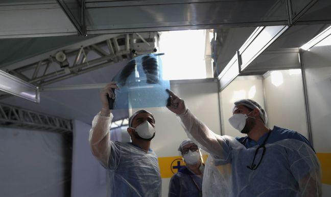 Médicos observam exame de paciente em hospital de campanha em Guarulhos (SP)