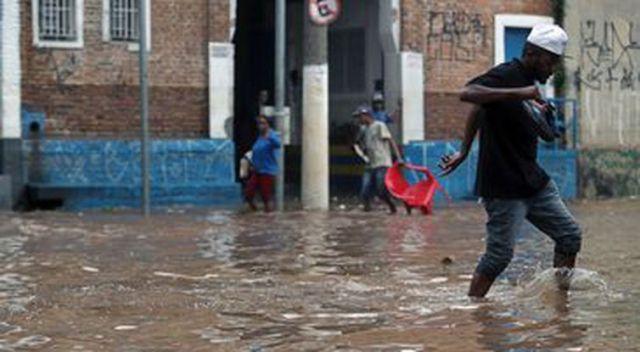 Pessoas caminham por uma rua inundada após fortes chuvas no bairro de Vila Prudente, em São Paulo.