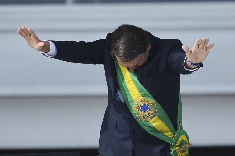 Presidente Jair Bolsonaro saúda o público depois de receber a faixa presidencial de Michel Temer, no Palácio do Planalto.