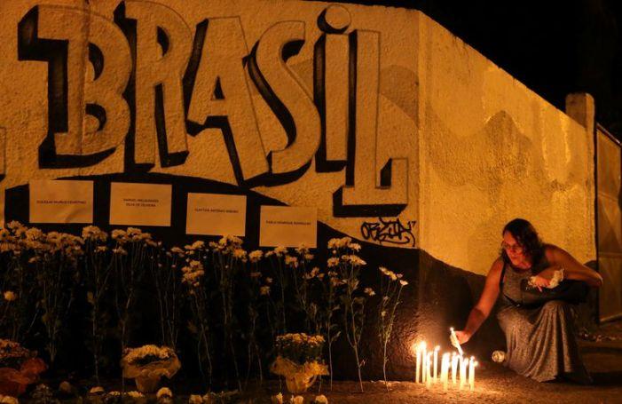 Uma mulher acende velas enquanto presta homenagem às vítimas do tiroteio na escola Raul Brasil em Suzano, São Paulo, Brasil 13 de março de 2019. REUTERS / Amanda Perobelli