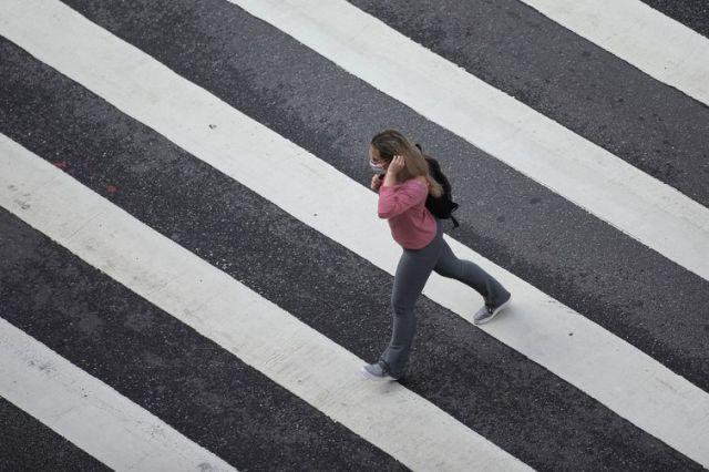 Mulher com máscara de proteção em avenida de São Paulo