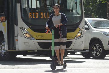 A atuária Samara Alce se locomove de patinete elétrico no centro do Rio de Janeiro.