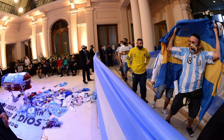 People pass by the coffin holding the body of soccer legend Diego Maradona during his wake at the presidential palace Casa Rosada, in Buenos Aires