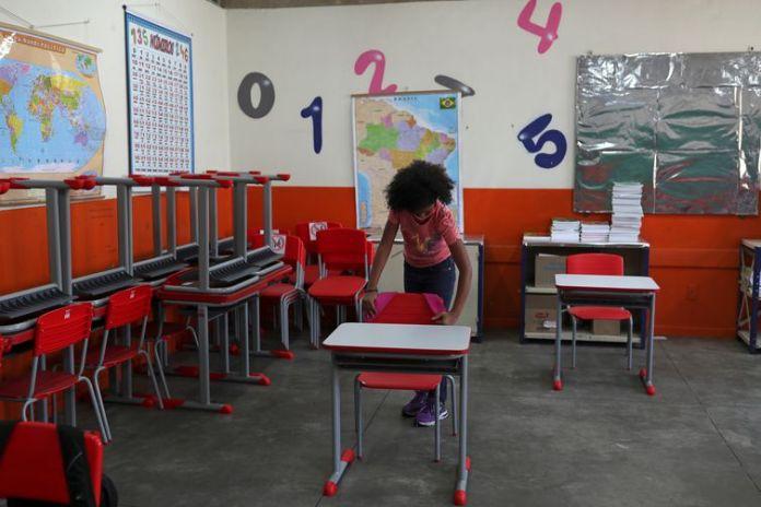 Criança pendura mochila na cadeira de sala de aula da escola Thomaz Rodrigues Alckmin, no primeiro dia de retorno das escolas do estado de São Paulo para atividades extracurriculares em meio ao surto de coronavírus (COVID-19) em São Paulo,