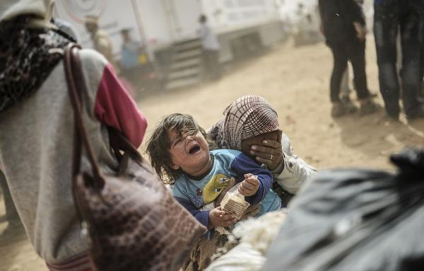 Criança síria chora com a mãe em campo de refugiados na fronteira da Turquia. (AFP).