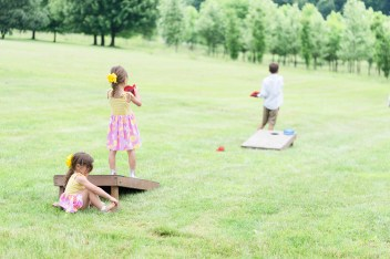 Children play cornhole during a summer wedding at Pinehall at Eisler Farm.