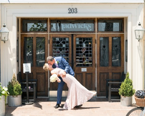 A groom kisses his bride in front of Chadwicks in Old Town Alexandria