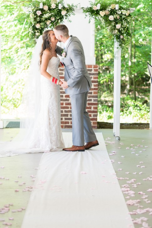 A bride and groom's first kiss during an American/Indian wedding at Westfields Golf Club in Clifton, Virginia. Photography by Erin Julius of Imagery by Erin.