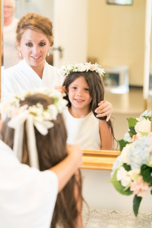 A bride and flower girl look into a mirror as they prepare for a wedding at The Citadel in Charleston, SC
