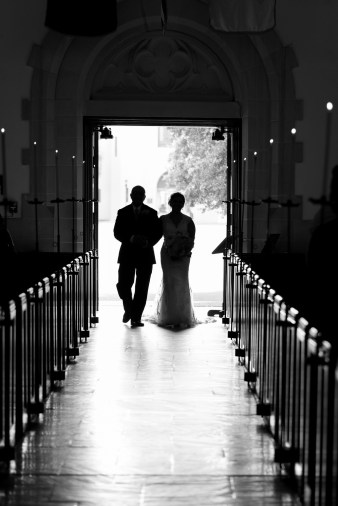 A bride and her father are silhouetted walking into the chapel at The Citadel during a wedding.