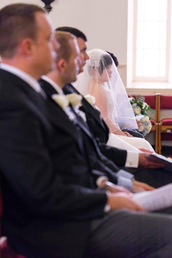 A bride sits with her veil over her face during a church wedding in Washington, D.C.