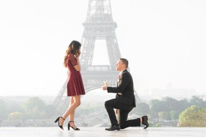 A groom holds out the engagement ring to his bride in front of the Eiffel Tower during an engagement session in Paris.
