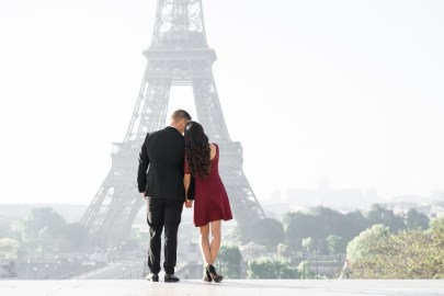 A couple looks out at the Eiffel Tower during their engagement session in Paris.