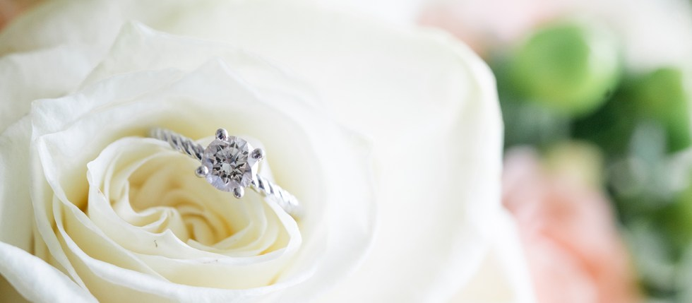 A close up of a diamond engagement ring tucked into a bride's bouquet.